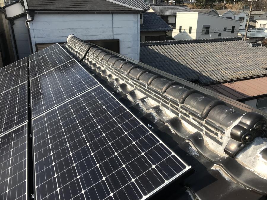 瓦の切妻屋根に太陽光が乗っています。