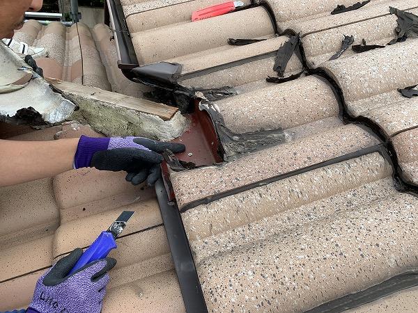 屋根修繕で棟と屋根の取り合いのコーキングを捲り、瓦を撤去します。