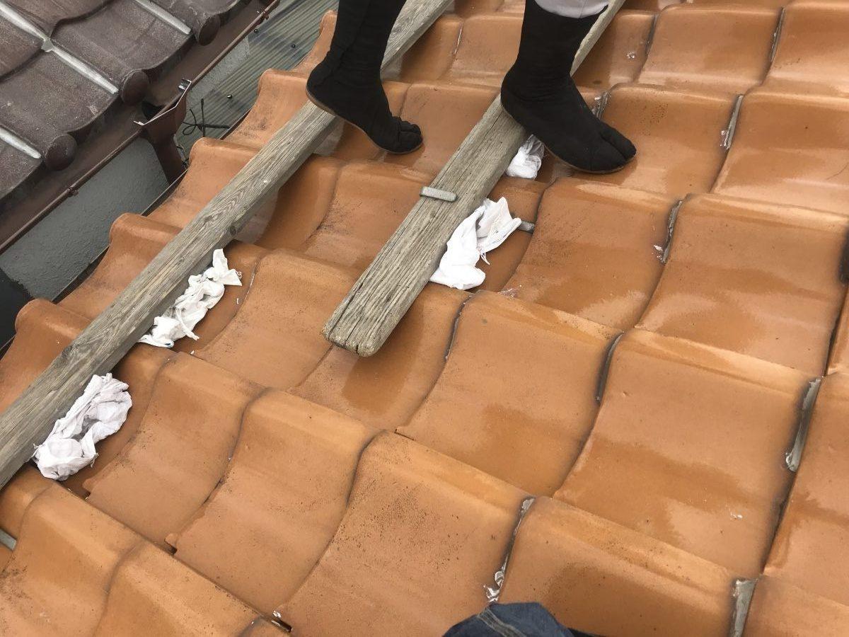 足場板の下に土嚢を詰め、土やゴミなどの転げ落ちを養生致します。