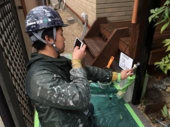 雨樋の上塗りの様子を写真を撮っている職人さんの写真