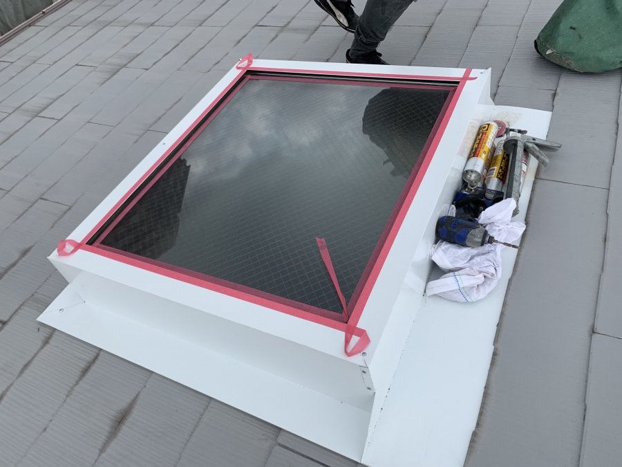 トップライト(天窓)の雨漏り修繕工事  トップライト板金とガラスの間をマスキングテープで養生します。