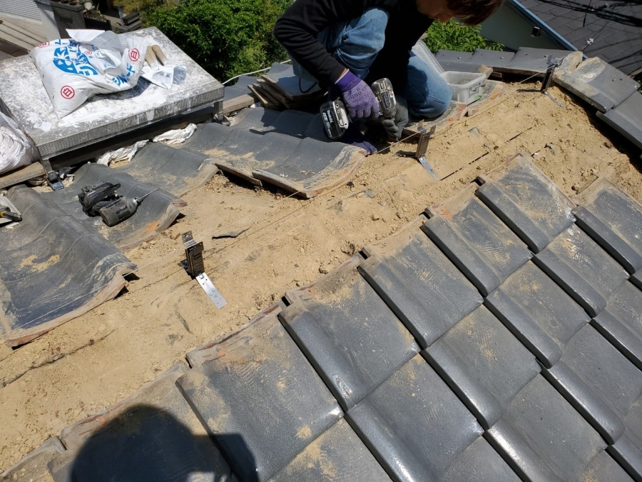 瓦屋根頂点に強力棟金物をビスで固定します。