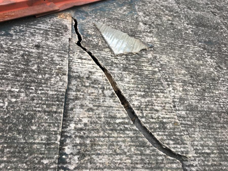 スレートの割れから屋根裏が見えています。